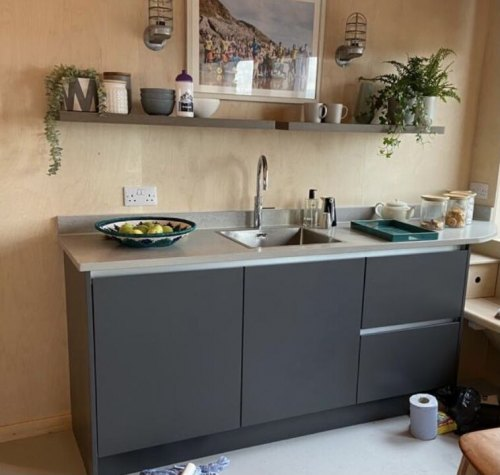 3 kitchen units with concrete effect worktop and open shelving with bowls and mugs
