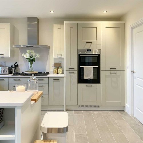 Cranbrook Stone and Cranbrook Ivory Symphony Kitchen shown with a kitchen penninsular which features a vase of flowers. Open shelving shows a selection of decorative items.
