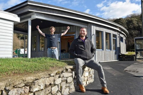 Two men infront of the surfability centre where Kitchens by emma reed donated kitchen units. Blue skies with clouds and grass on the front of the centre