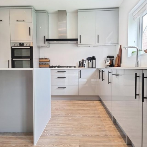Gloss grey Woodbury kitchen with kitchen island shown with white worktops and black skinny handles. wooden and matt black accessories are also shown