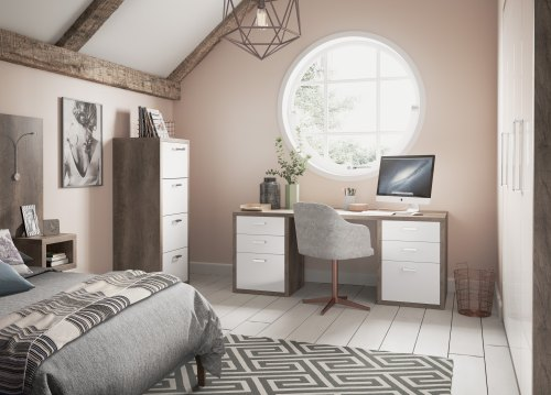 a bedroom space with a desk and a set of drawers in a pink walled room with a large circular window. A bed with bedding on is shown
