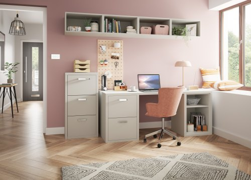 pink room with gemoetric floor with a desk, filing cabinet and 4 shelves. laptops, lamps and other office accessories are shown