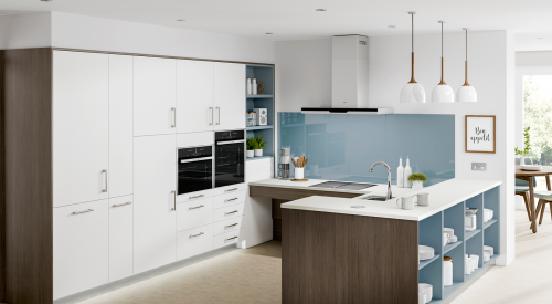 Image shows on of the Freedom Accessible Kitchens in white and dark oak, featuring a blue splashback and blue open shelving. A corner worktop is shown with leg space that moves up and down