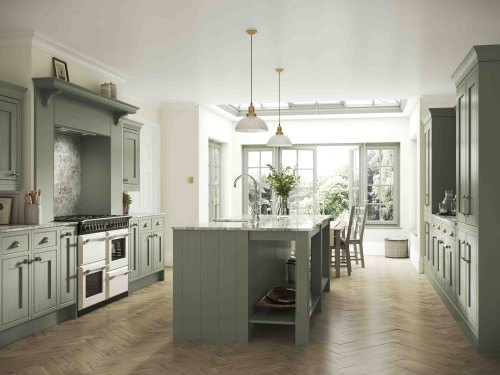 this shows and example set of atlantic green kitchens. a light green shaker inframe kitchen is shown with a kitchen island and brass finish handles. The worktop is a marble effect and there are a selection of muted toned decor items