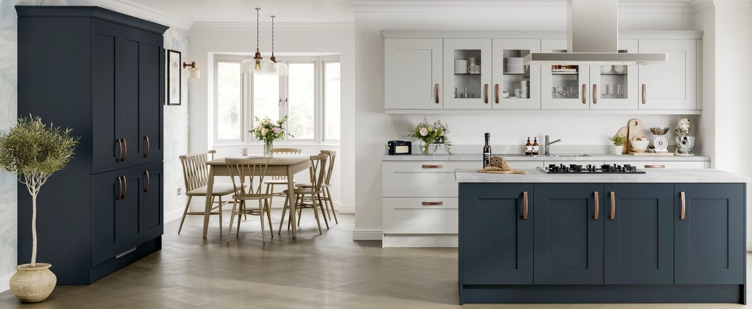 Navy Blue kitchen island with a muted gray wall unit and pantry. A dining table is shown and there are gemoetric tiles on the walls.
