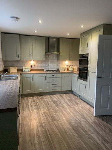Cranbrook Sage kitchen with woodern worktops and flooring featuring stainless steel handles