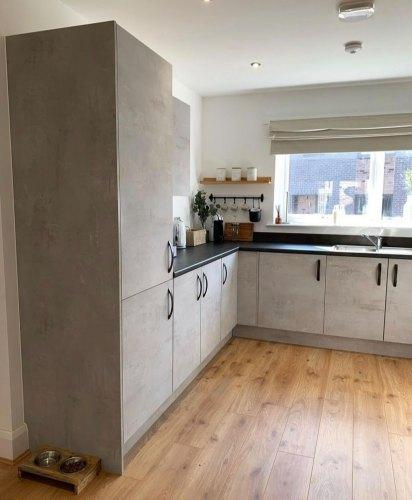 Concrete effect kitchen with matt black handles