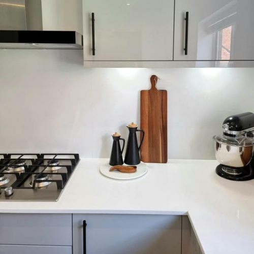 Gloss grey Woodbury kitchen shown with white worktops and black skinny handles. wooden and matt black accessories are also shown