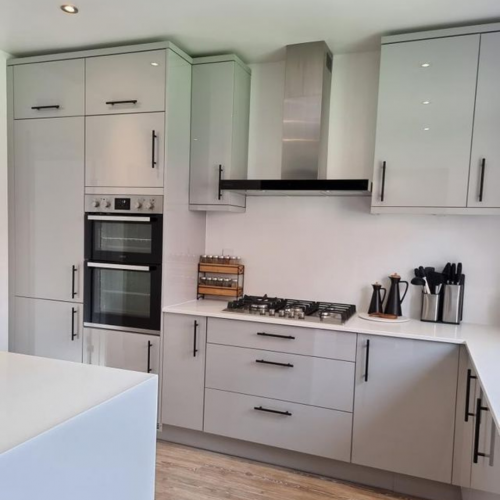 Home of MySymphonyStyle April winner which is a gloss grey kitchen with white worktops and black handles. Kitchen accessories are shown on the site including wine rack and knife block. Hob, oven and extractor is shown