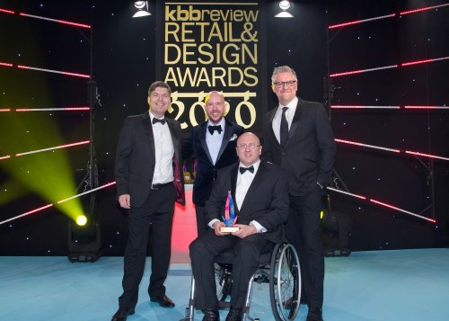 "Adam Thomas sits in the middle of three men, all dressed smart in tuxedo with a sign behind that reads ' KBB Review Retail Design Awards 2020"" His award was given for his effort creating accessible kitchens with adam thomas"