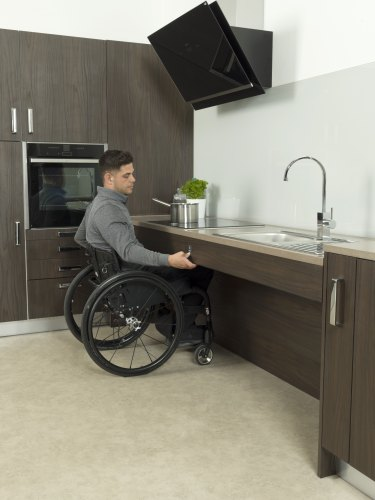 Man using wheelchair is pressing the button to allow a worktop to rise and fall as part of a kitchen adaptations project