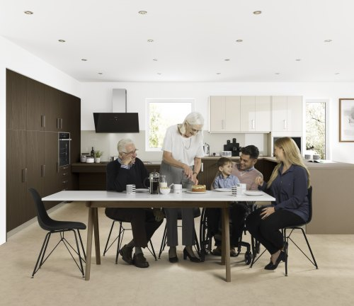 A family of multiple generations is sat round a dining table in an accessible kitchen eating cake in a kitchen which has been a kitchen adaptations project for the wheelchair user in the family. The kitchen shows kitchen adaptation in the form of a rise and fall worktop and specialist units