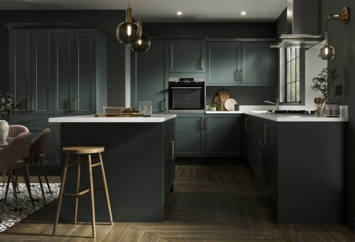 A Dark Green shaker Symphony kitchen with white worktops and dark wooden floors, along with wooden bar stools and brass handles and detailing such as lighting