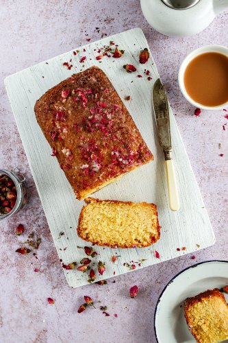 Lemon and Rose Drizzle Cake laid on a chopping board surrounded by dried rose petals. There is a knife on the chopping board and a cup of tea to the side of the board