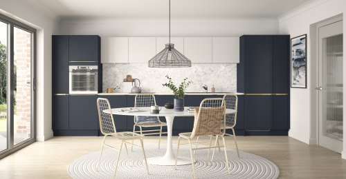 Matt white and Indigo kithen with a kitchen table in the centre. Marble effect worktops and tables with rattan effect chairs and a hanging pendant light.