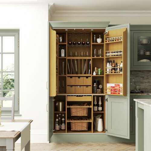 an open kitchen pantry in an atlantic green kitchen showing oak finish internals and a selection of kitchenware stored within it
