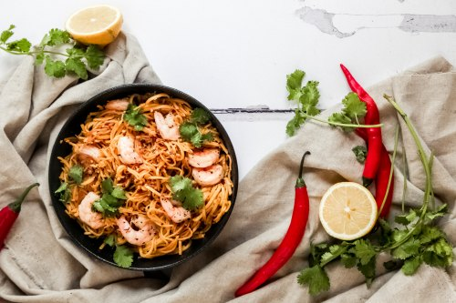 Spicy King Prawn Stir Fry in a bowl, surrounded by chillies, coriander and lime