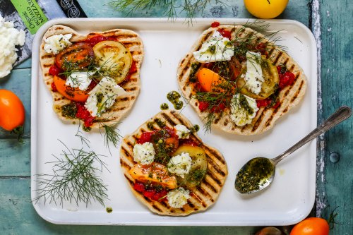 Grilled flatbreads covered in mozzarella, tomatoes, person and herbs on a white tray with herbs