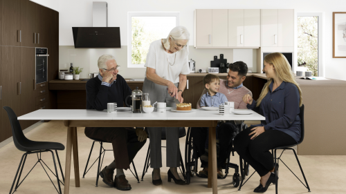 Family are sat around a table with a dark wooden effect freedom accessible kitchen design in the background. One family member is a wheechair user and there is young child sat on his lap looking at cake