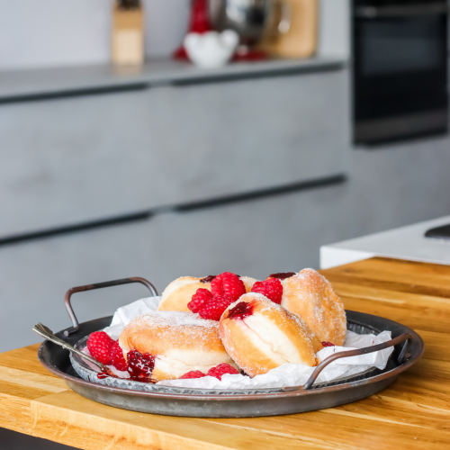 Brioche Doughnuts on a cast iron style place on a wooden chopping board. A concrete effect Symphony Urban kitchen is shown in the background.