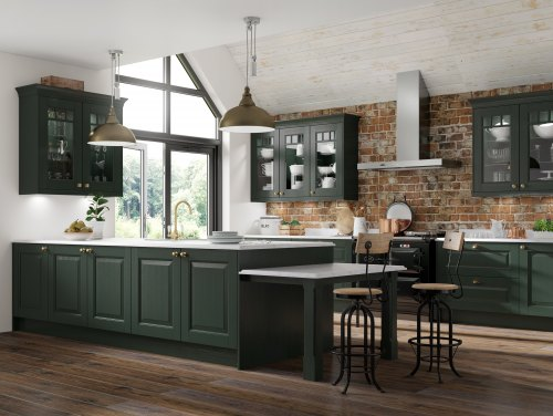 Large kitchen with wooden floors and brick wall detailing. Kitchen is a panelled door with raised centre and in a very deep green shade. worktops are white and there are copper accessories throughout including two bar stools