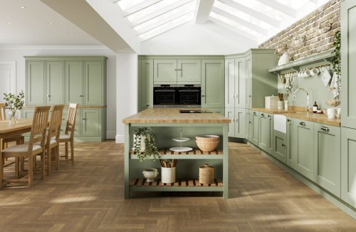 A pale green laura ashley whitby kitchen with wooden floor and wooden worktops shown with a kitchen island